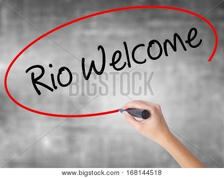 Woman Hand Writing Rio Welcome With Black Marker Over Transparent Board.