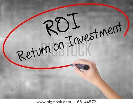 Woman Hand Writing Roi  Return On Investment With Black Marker Over Transparent Board