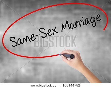 Woman Hand Writing Same-sex Marriage With Black Marker Over Transparent Board
