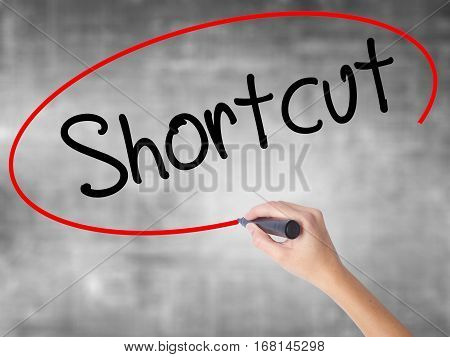 Woman Hand Writing Shortcut With Black Marker Over Transparent Board