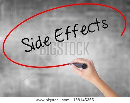 Woman Hand Writing Side Effects With Black Marker Over Transparent Board