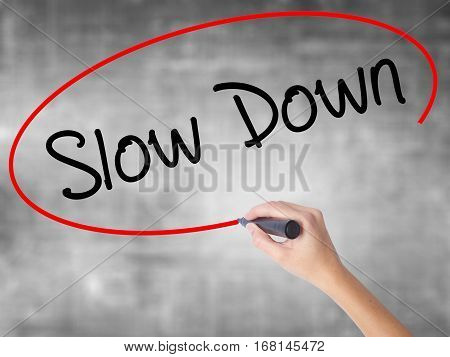 Woman Hand Writing Slow Down With Black Marker Over Transparent Board