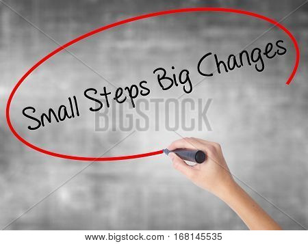 Woman Hand Writing Small Steps Big Changes With Black Marker Over Transparent Board