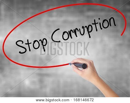 Woman Hand Writing Stop Corruption With Black Marker Over Transparent Board.