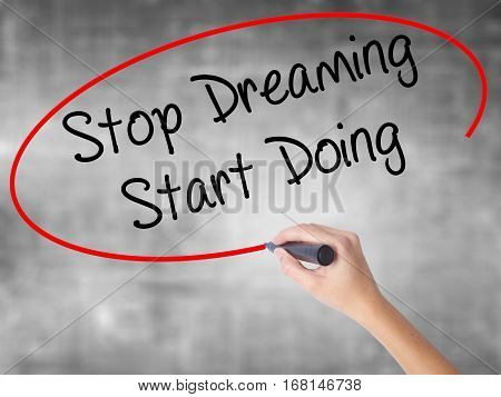 Woman Hand Writing Stop Dreaming Start Doing  With Black Marker Over Transparent Board