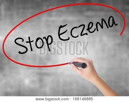 Woman Hand Writing Stop Eczema With Black Marker Over Transparent Board