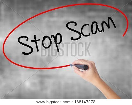 Woman Hand Writing Stop Scam With Black Marker Over Transparent Board