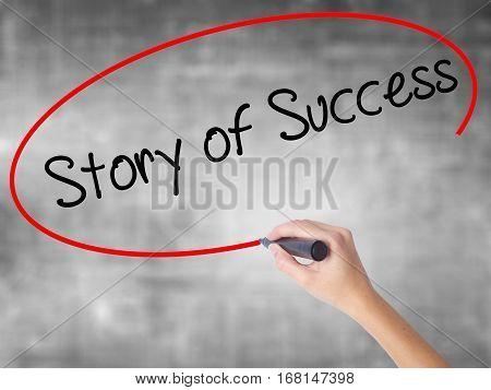 Woman Hand Writing Story Of Success With Black Marker Over Transparent Board