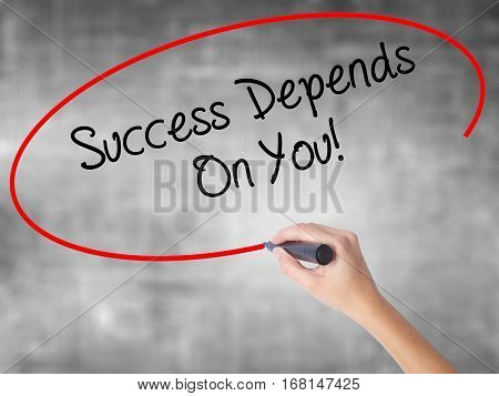 Woman Hand Writing Success Depends On You! With Black Marker Over Transparent Board
