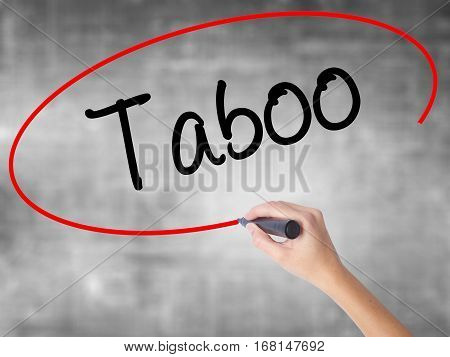 Woman Hand Writing Taboo With Black Marker Over Transparent Board