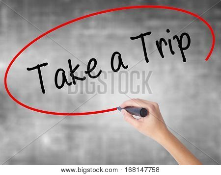 Woman Hand Writing Take A Trip With Black Marker Over Transparent Board