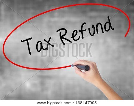Woman Hand Writing Tax Refund With Black Marker Over Transparent Board