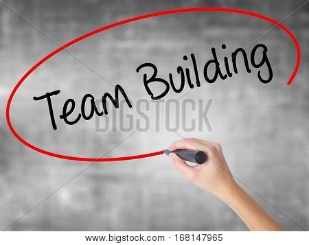 Woman Hand Writing Team Building With Black Marker Over Transparent Board