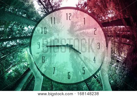 Time change concept. Double exposure of female hands holding clock and trees background