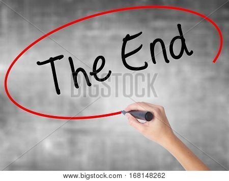 Woman Hand Writing The End With Black Marker Over Transparent Board