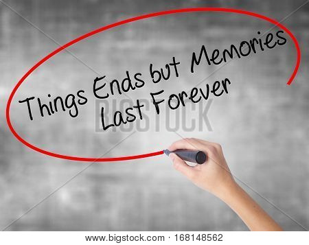 Woman Hand Writing Things Ends But Memories Last Forever With Black Marker Over Transparent Board
