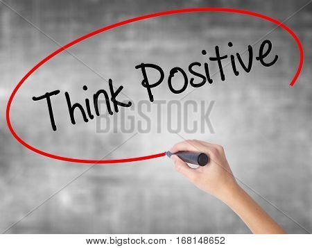 Woman Hand Writing Think Positive With Black Marker Over Transparent Board