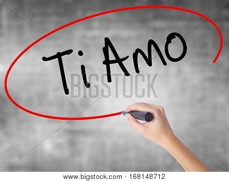 Woman Hand Writing Ti Amo (i Love You In Italian) With Black Marker Over Transparent Board.