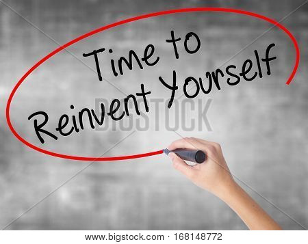Woman Hand Writing Time To Reinvent Yourself With Black Marker Over Transparent Board