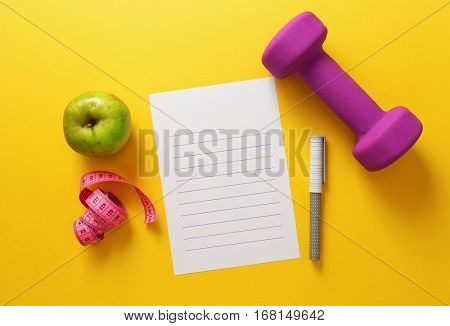 Healthy lifestyle and sports. Blank lined paper with pen, dumbbells, apple and tape measure on yellow background.