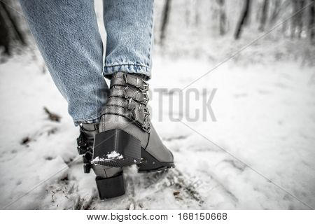 Woman shoes in the snow, glam silver leather boots
