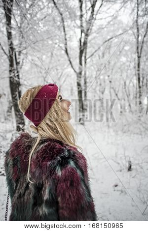 Winter Portrait Of Woman Posing In The Snowy Forest Wearing A Warm Fur Jacket, Looking At The Trees