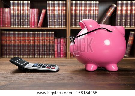 Close-up Of A Piggybank And Calculator On Wooden Desk In Courtroom