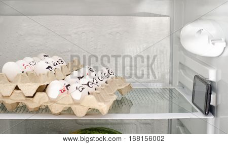 Eggs in trays on a shelf of the refrigerator located as in a movie theater. Painted faces looking at phone