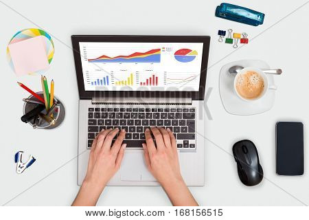High Angle View Of A Person Hand Analyzing Financial Graph On Laptop At Office Desk