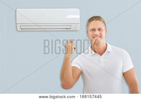 Portrait Of A Young Man Using Air Conditioner At Home