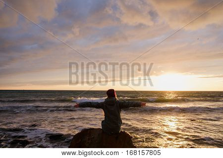 young woman sitting on a rock on the beach and looking at stormy sea and sunset sky. rear view