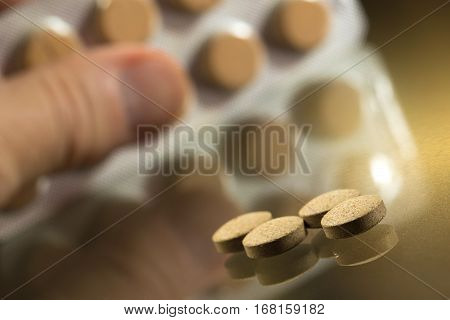 Man takes vitamin painkiller pills from the set