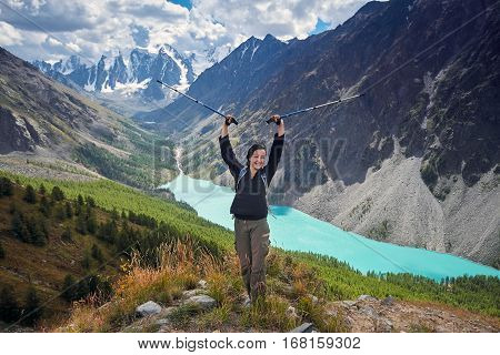 Brave girl conquering mountain peaks of the Altai mountains. The majestic nature of the mountain peaks and lakes. Hiking in rugged places. Journey through Russia Siberia Aktru and shavlinskoe lake