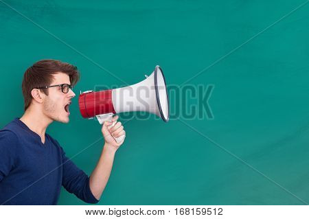 Young Man Doing Announcement Using Megaphone On Blackboard