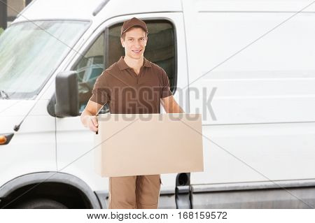 Portrait Of A Happy Delivery Man Of Mover Holding Box Outside The Van Or Truck