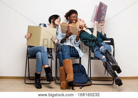 Different Ethnic Students Sitting In Chairs