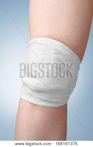 Injured female knee with white gauze bandage