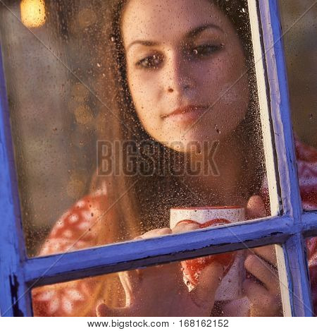 Pretty woman in warm room indoor at home in winter night. Drinking tea looking away. Candid shot from outdoor trough the window.