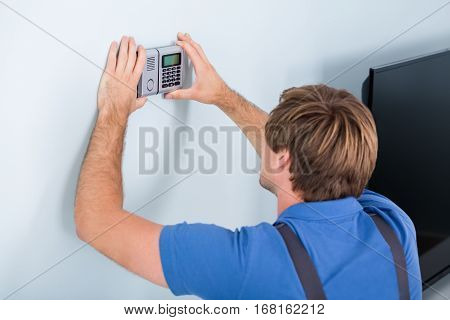 Rear View Of Repairman Installing Security System Against Wall