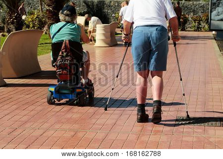 Disabled men on power wheelchair and with crutchers walk on promenade outdoors on sunny summer day on flagstone pavement on terracotta background
