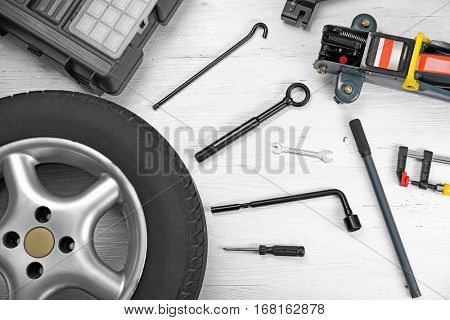 Car wheel with tools on wooden background