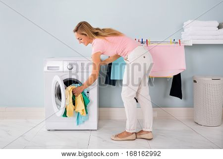Smiling Woman Loading Untidy Clothes In Washing Machine In Utility Room