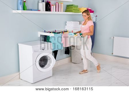 Young Smiling Woman With Basket Of Clothes Near Washing Machine In Utility Room