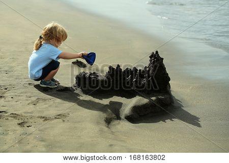 Cute Baby Boy Builds Sandcastle On Sea Beach