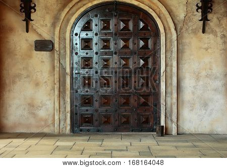 Old wooden arch door medieval style portal in dark brown color on stone building on cracked cement wall background