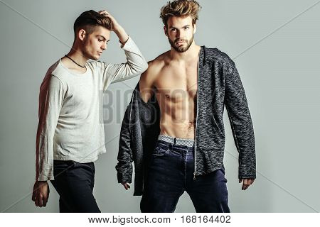 Handsome young bearded men friends in shirt and bare torso has fashionable hair and serious face on grey background. Stylish sexy guys with muscular body in studio