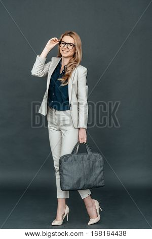 Young and smart. Full length of confident young woman in smart casual wear adjusting her eyeglasses and looking at camera while standing against grey background