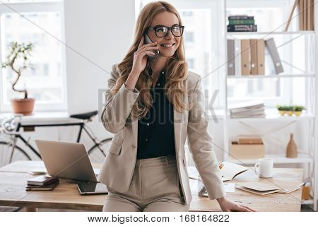 Pleasant business talk. Confident young woman in smart casual wear talking on the mobile phone and smiling while leaning on desk in creative office