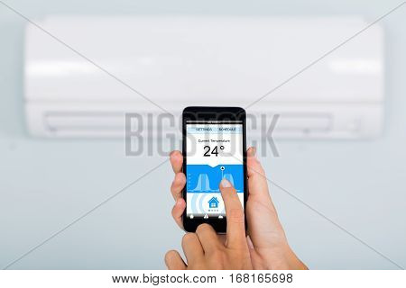 Close-up Of Woman Hand Setting Temperature Of Air Conditioner Using Mobile Phone App At Home