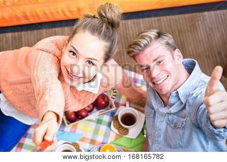 Cheerful couple taking selfie at breakfast lying on the living room floor - Happy young friends share fun moments together using mobile phone stick at home - Concept of daily healthy life together